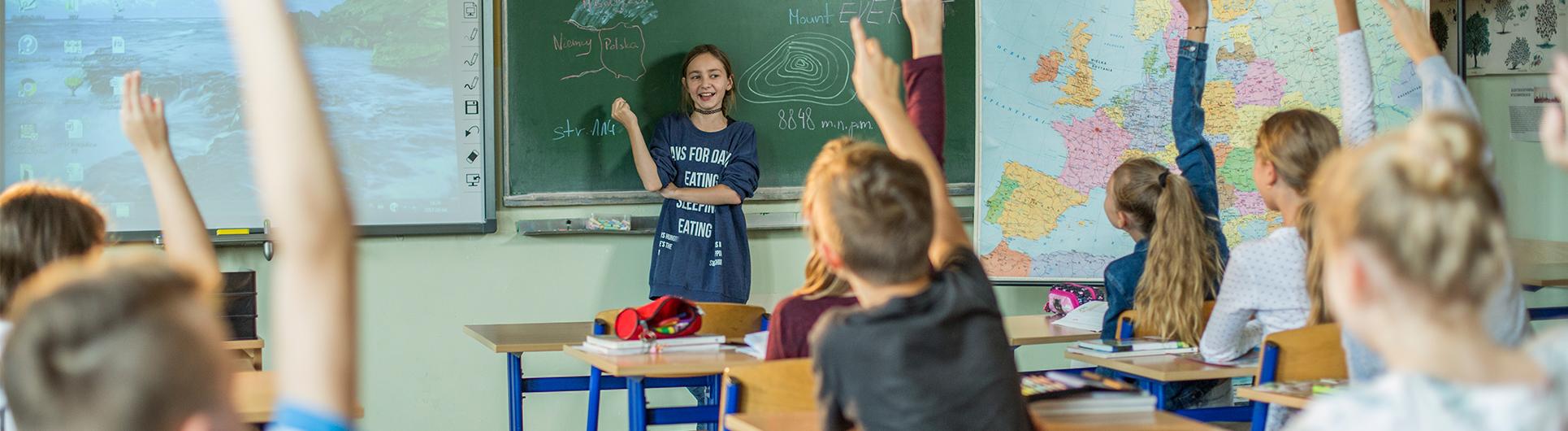 dzieci zgłaszają się pdoczas lekcji, jedna uczennica stoi przy zielonej tablicy