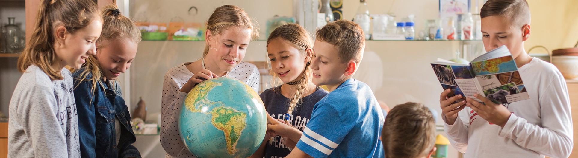 dzieci w klasie oglądają globus